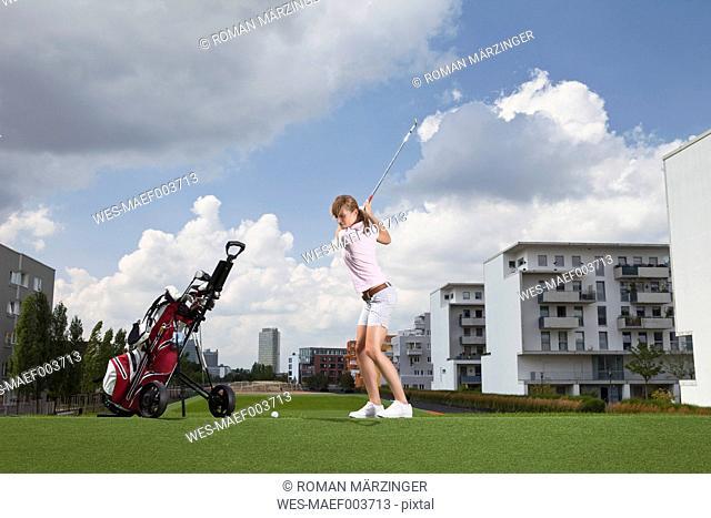 Germany, Bavaria, Munich, Young woman playing city-golf