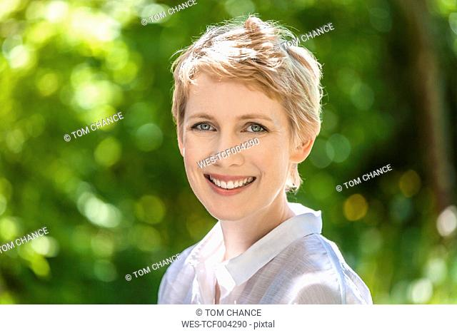 Portrait of smiling woman with short blond hair