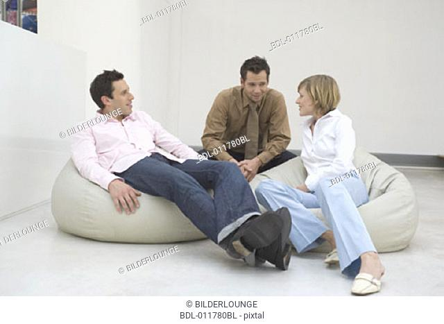three people relaxing on bean bags and talking