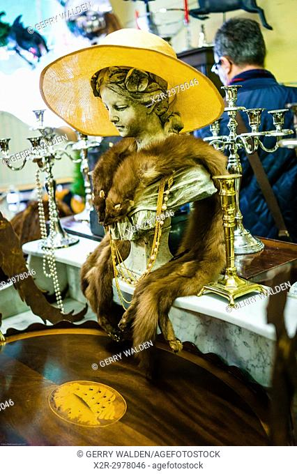 Animal pelts and a yellow hat adorn an artistic bust inside an antique shop in Bath, Somerset