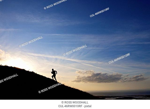 Silhouette of hiker running up hillside