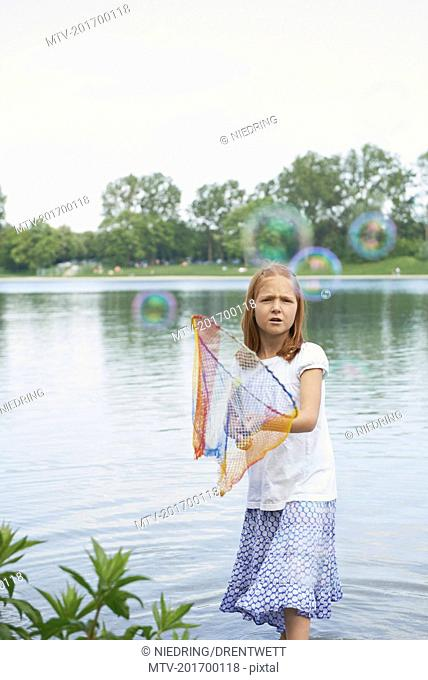 Girl catching soap bubbles with fishing net in the lake, Bavaria, Germany