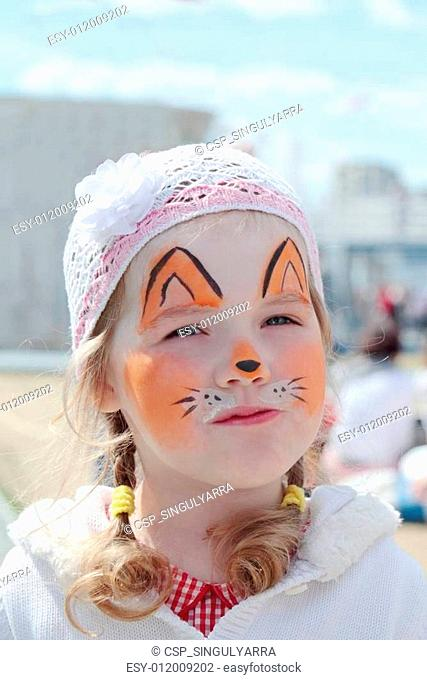 Little beautiful girl with face painting of orange fox