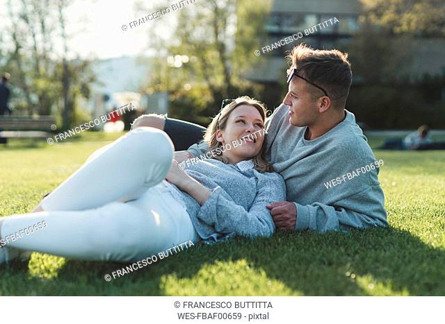 Young couple relaxing on a meadow at sunlight