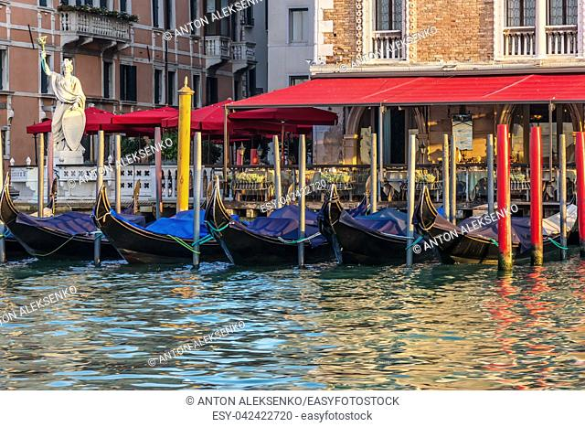 Gondolas near an italian street cafe in the Grand Canal of Venice