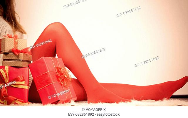 Christmas winter happiness concept. Woman legs wearing red pantyhose with many presents gift boxes