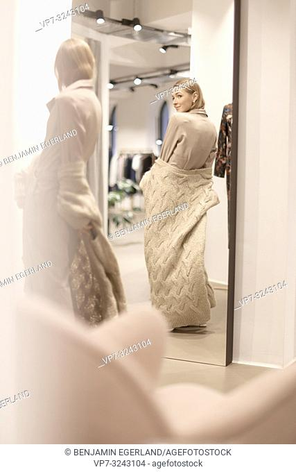 fashionable woman checking her beige outfit style in mirror in clothing store, wearing cool stylish one piece jumpsuit, women's fashion clothing, from behind