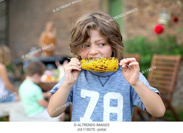 Boy Eating Sweetcorn Outdoors At Home In Garden