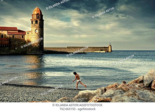 Boy on the beach and Notre-Dame des Anges church in background, Collioure. Roussillon-Languedoc, Pyrenees Orientales, France