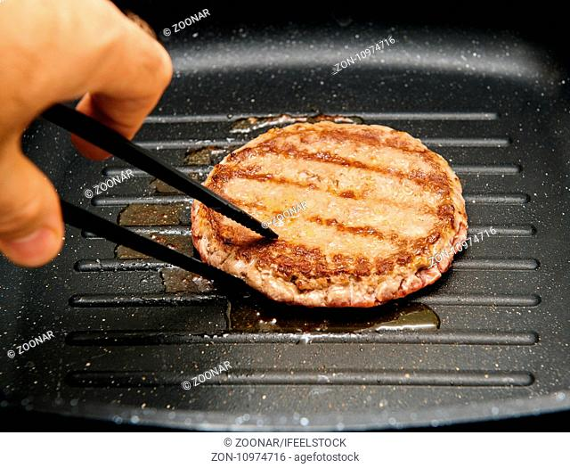 Turning delicious burger preparation in grill pan at home