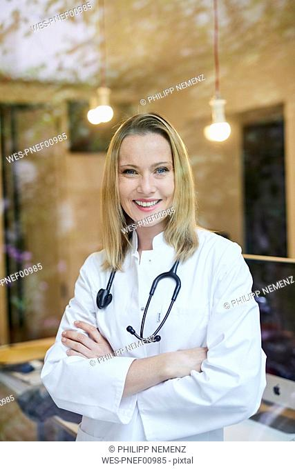 Portrait of smiling female doctor with stethoscope behind windowpane