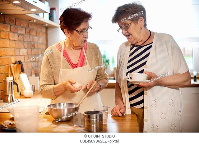 Senior adult women drinking coffee and baking