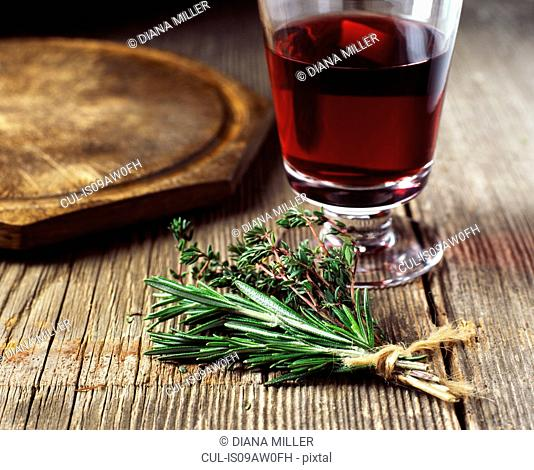 Bunch of rosemary and thyme tied with string, red wine
