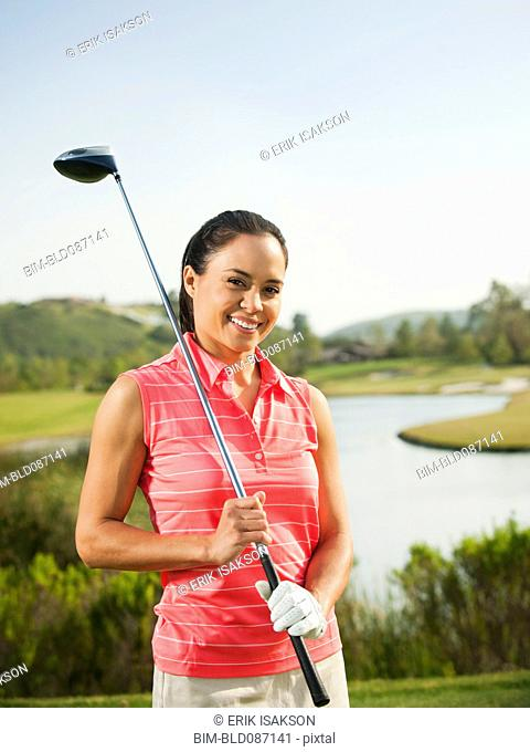 Mixed race woman holding golf club on golf course