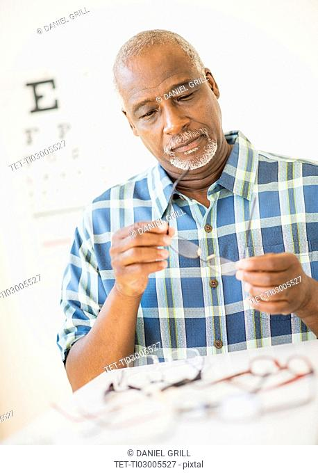 Man looking at glasses in store