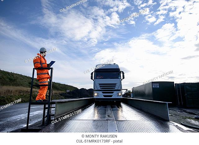 Worker directing truck on scales
