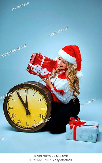 Girl dressed in santa hat with a Christmas decorations. She looking at camera. Holiday concept with blue background