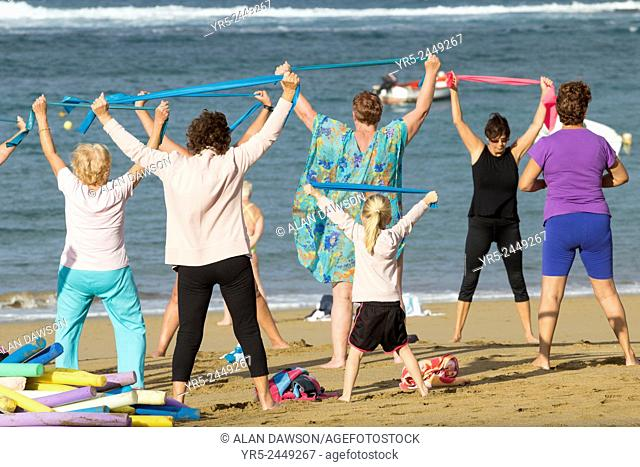A group of elderly local women are joined by a young girl at their daily exercise class on Las Canteras beach in Las Palmas, Gran Canaria, Canary Islands, Spain