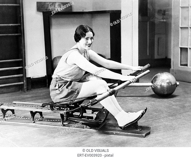 Woman using rowing machine All persons depicted are not longer living and no estate exists Supplier warranties that there will be no model release issues