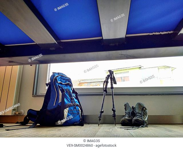 Boots, backpack and walking sticks in the floor of a hostel in Palas de Rei, Way of St. James, Galicia, Spain. Under bed view