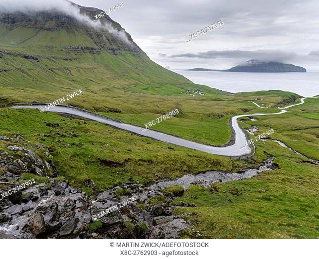 Mountain road to the Nordradalur at the west coast. Koltur island in the background. The island Streymoy, one of the two large islands of the Faroe Islands in...