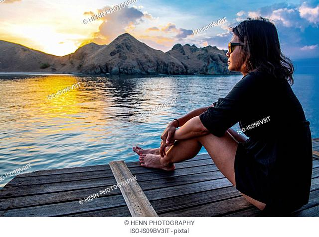 Female tourist watching sunset from sailboat, Komodo Island, East Nusa Tenggara, Indonesia