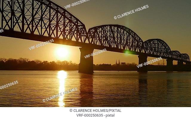 The sun rises behind the Big Four Bridge on the Ohio River in Louisville, Kentucky