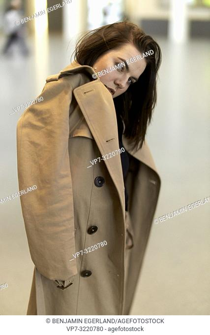 portrait of fashionable confident woman indoors, hiding behind fashion coat, blogger, in Munich, Germany