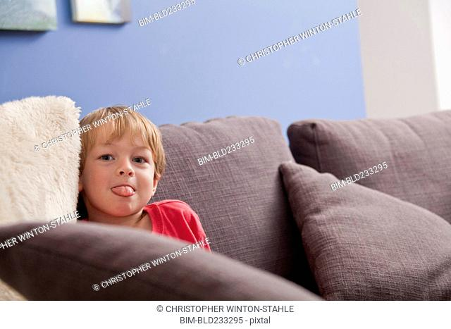 Caucasian boy with tongue out on sofa