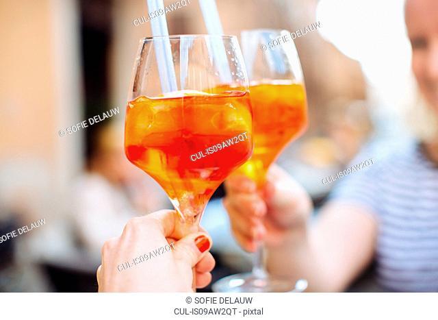 Two women raising a glass of aperol spritz, Ferarra, Italy