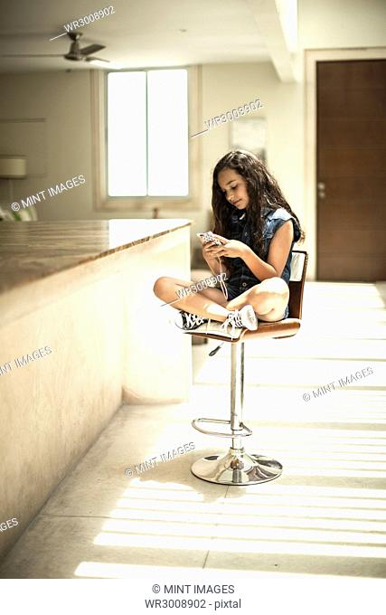 A girl sitting at a kitchen counter looking at a mobile phone screen