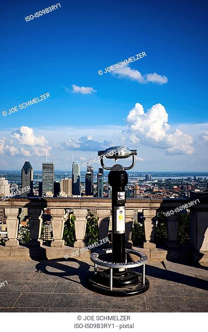 Coin operated binoculars and downtown cityscape with blue sky, Montreal, Quebec, Canada