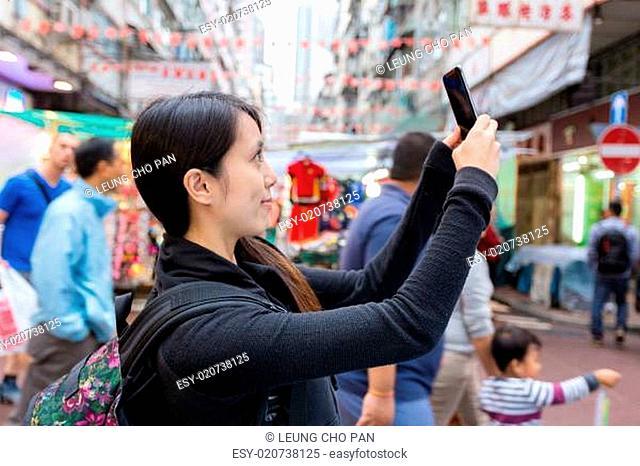 Young tourist woman taking selfie at street maket in Hong Kong