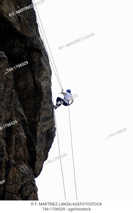 Girl making a mountain rappelling on a rock wall
