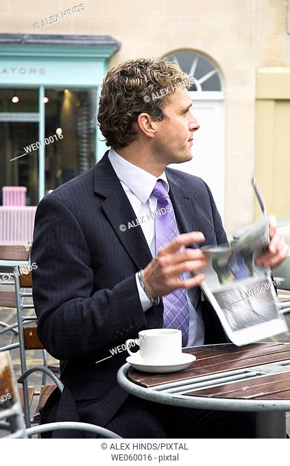 Young businessman sitting outside at a cafe with a newspaper. Shot in Bath, United Kingdom