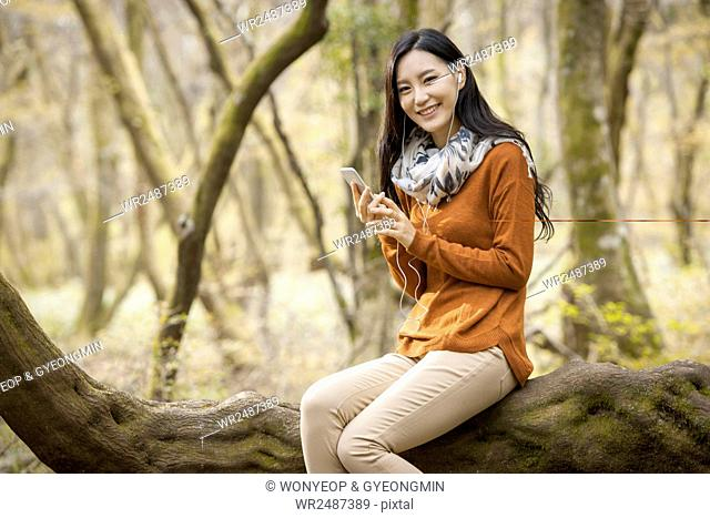 Young smiling woman sitting on a branch listening to music in forest in fall
