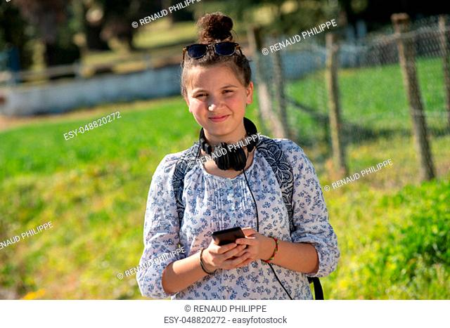 a young teenager girl waiting the school bus and using her smartphone