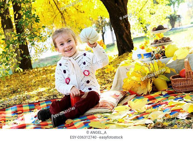 Happy girl showing hand-made pumpkin under autumn trees