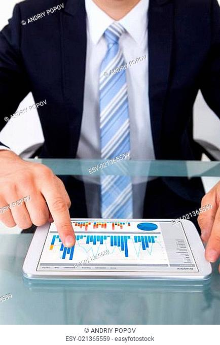 Businessman Comparing Graphs On Digital Tablet In Office
