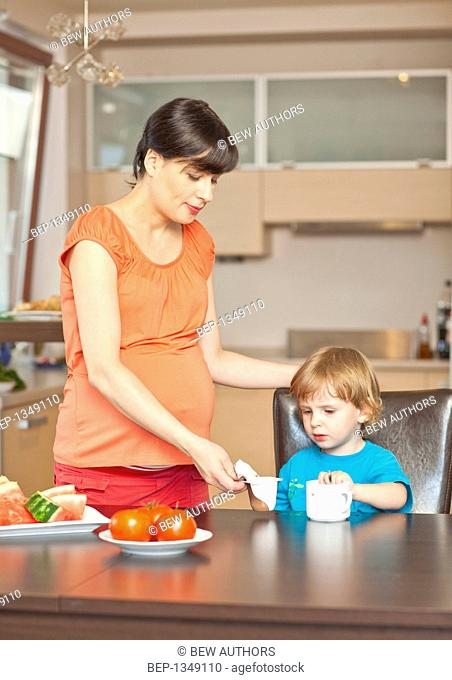 Pregnant woman and her son eating breakfast together