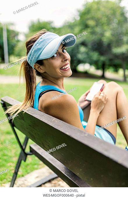Young woman in sports wear using smart phone, sitting on bench