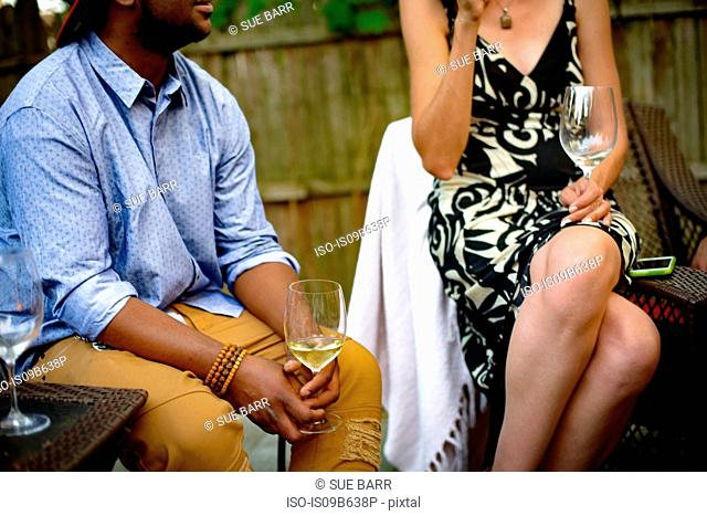 Man and woman at garden party, sitting, in conversation, holding wine glasses, mid section