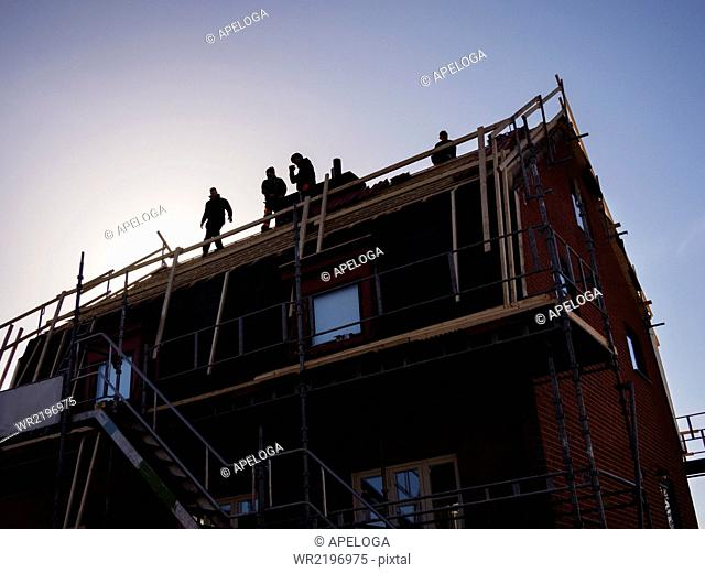 Silhouette of men working at construction site