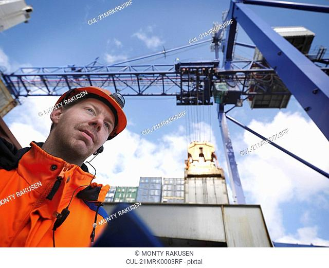 Sailor inspects cargo under gantry crane