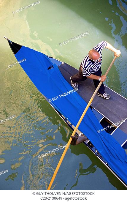 Gondolier on his gondola, Venice, Italy
