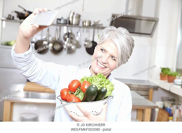 Mature woman holding colander with vegetables taking selfie