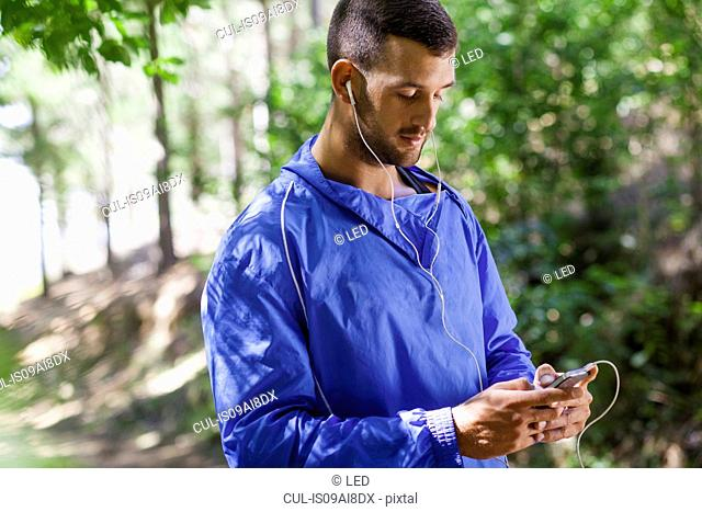 Male jogger using mp3 in forest
