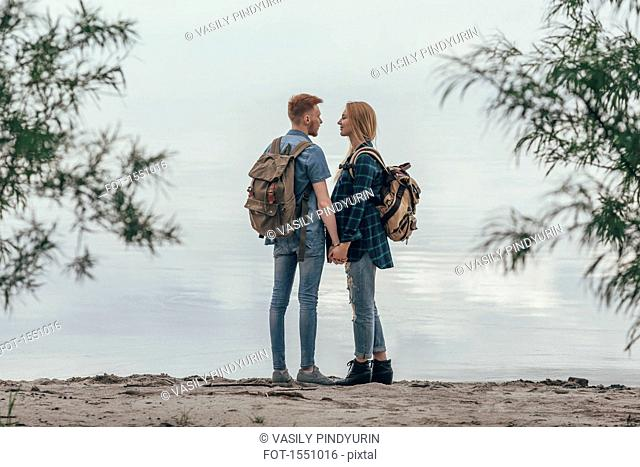 Couple holding hands while standing on lakeshore