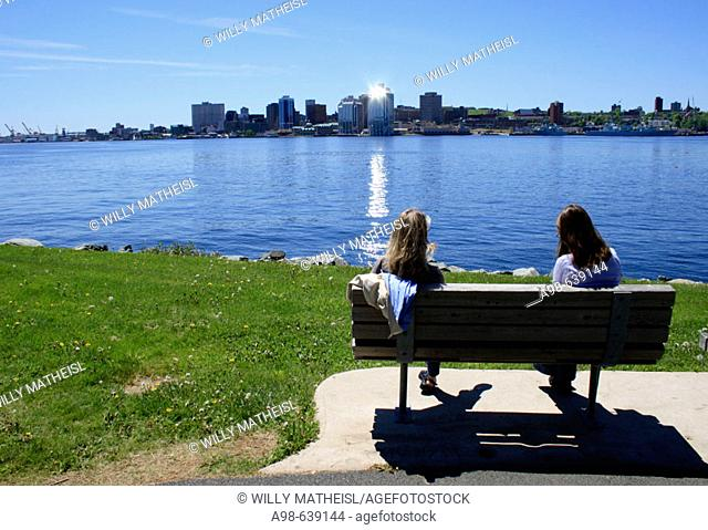 2 girls sitting on bench. Dartmouth. Halifax. Nova Scotia. Canada