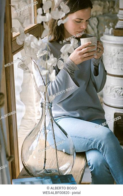 Woman sitting on window sill at home drinking tea